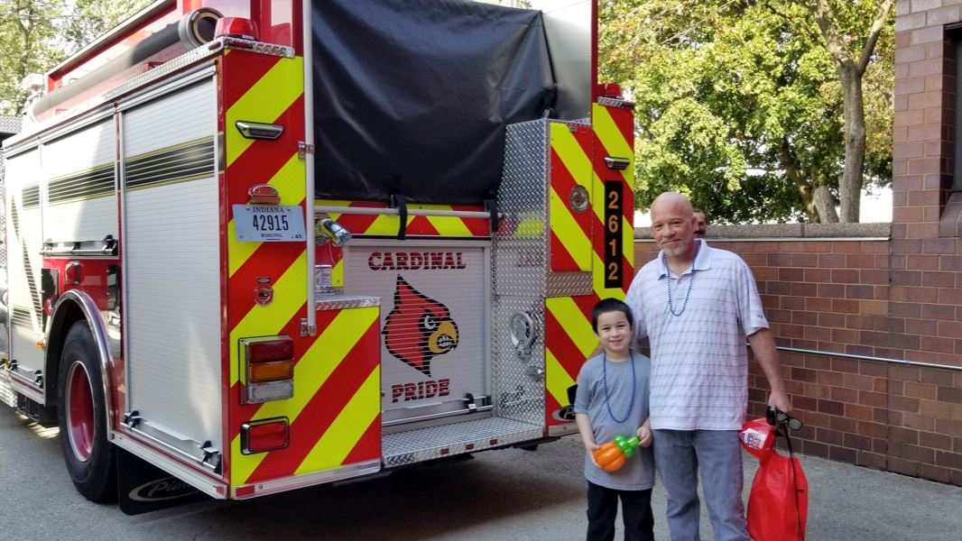 Father and Son Smiling Next to a Firetruck