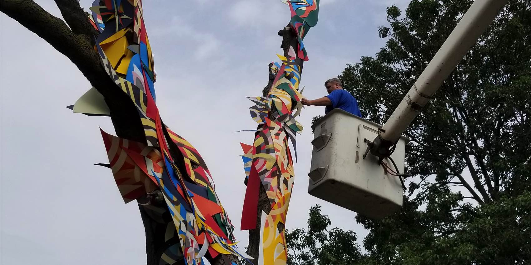 Public Worker Decorates a Tree With Colorful Paper Patterns